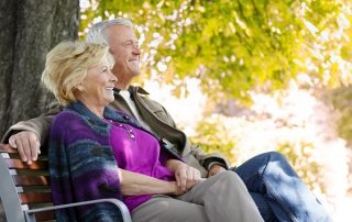 Senior couple relaxing together on a sunny autumn day at park